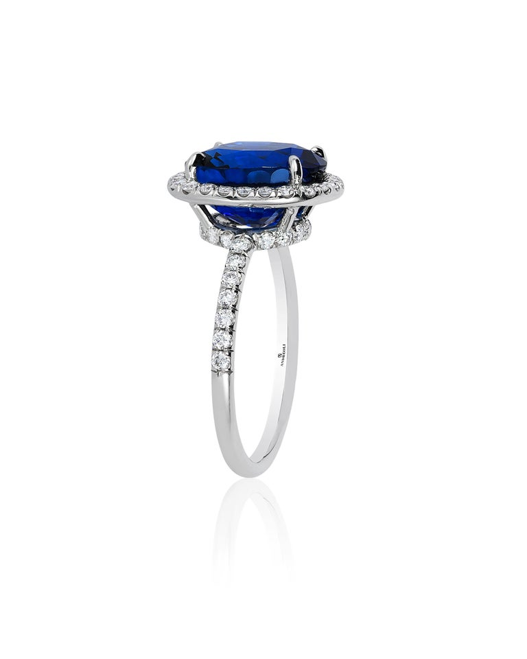 Andreoli CDC Certified 6.31 Carat Ceylon Blue Sapphire Diamond Platinum Ring. This ring features a 6.31 carat vivid blue cushion Ceylon blue sapphire certified by C. Dunaigre Consulting Switzerland surrounded with 0.56 carats of round brilliant