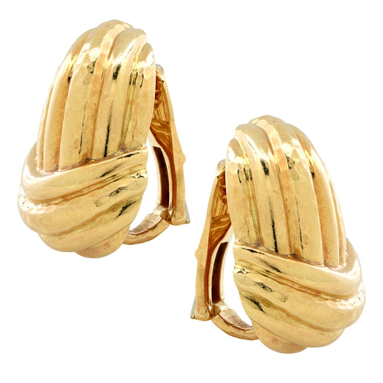 Striking Andrew Clunn clip-on earrings circa 1980, crafted in 18 karat yellow gold. Clunn mixes hammered and polished gold to create this masterpiece which exemplifies Clunn's elegantly chic and bold style. These stunning earrings measure 1 inch in