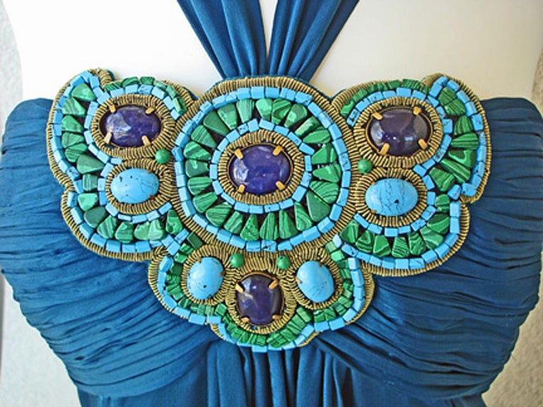 Designer to the stars, Paris designer Andrew Gn's extravagant jeweled bias cut halter gown in a rich deep shade of teal blue. Layers of silk chiffon in an empire waist style with ruched bodice adorned with large malachite, lapis, and turquoise prong