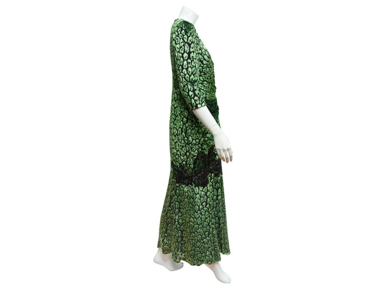 Product details:  Metallic green animal-print gown by Andrew Gn.  Accented with black beaded lace panels.  V-neck.  Elbow-length sleeves.  Surplice bodice.  Concealed back zip closure.  38