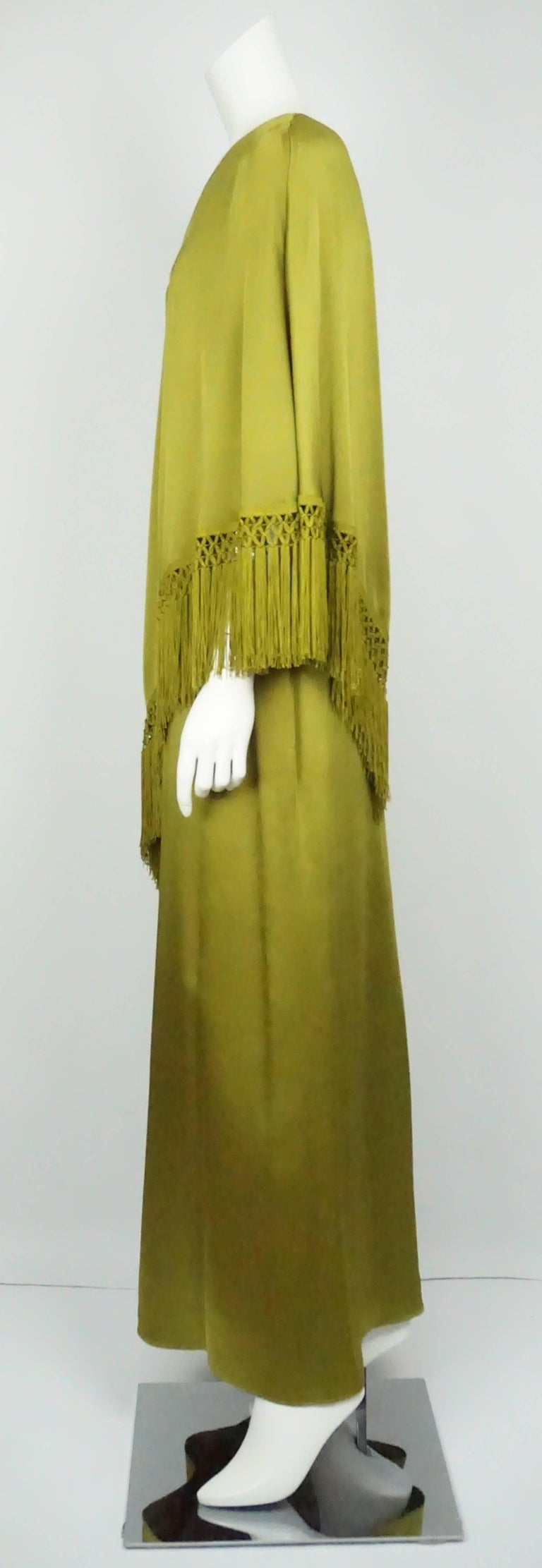 Andrew Gn Olive Green Silk One Shoulder Gown w/ Fringe - 40 This dramatic yet beautiful Andrew Gn dress is silk with a one shoulder poncho like top with fringe. There is a back zip with a unique woven detailing and it is floor length.  Measurements: