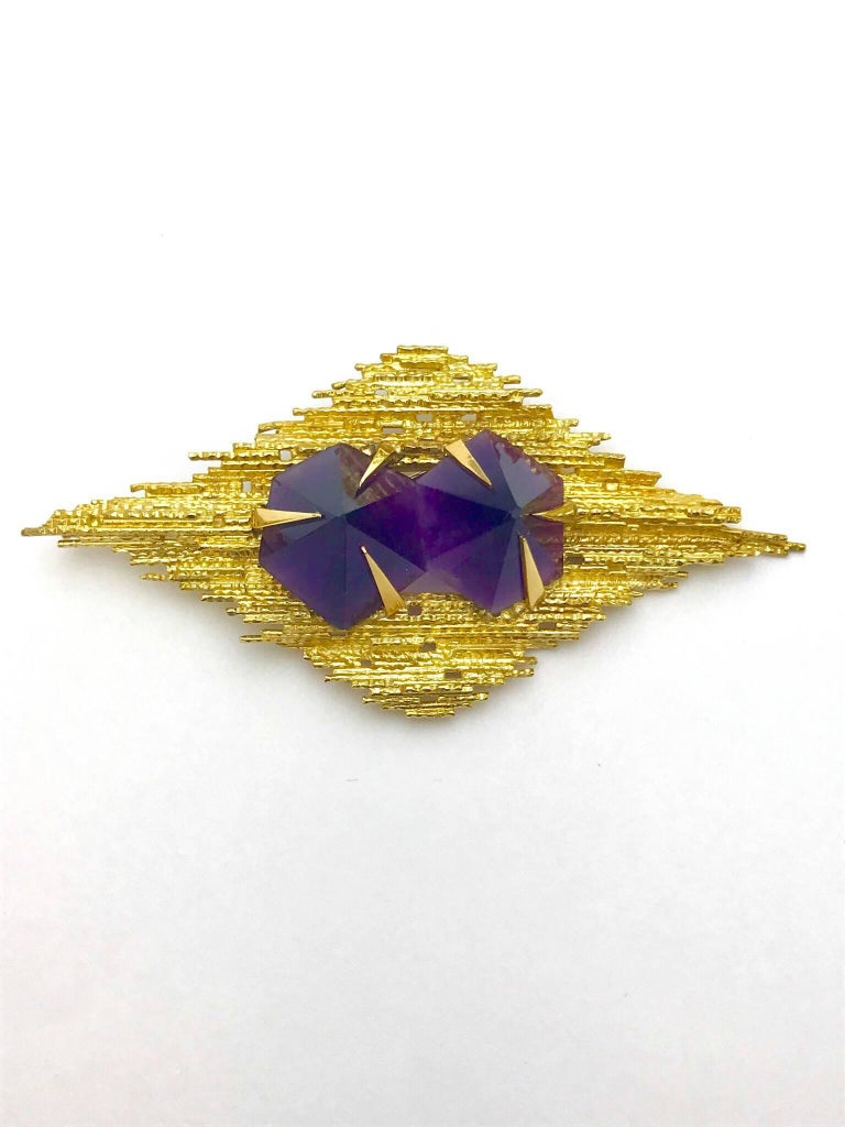 An Andrew Grima amethyst and 18 karat yellow gold pendant brooch. created in the fashion of many of his pieces, the two conical cut amethyst have a total weight of 45.80 carats, set with large pointed prongs, in a textured yellow gold frame.  The