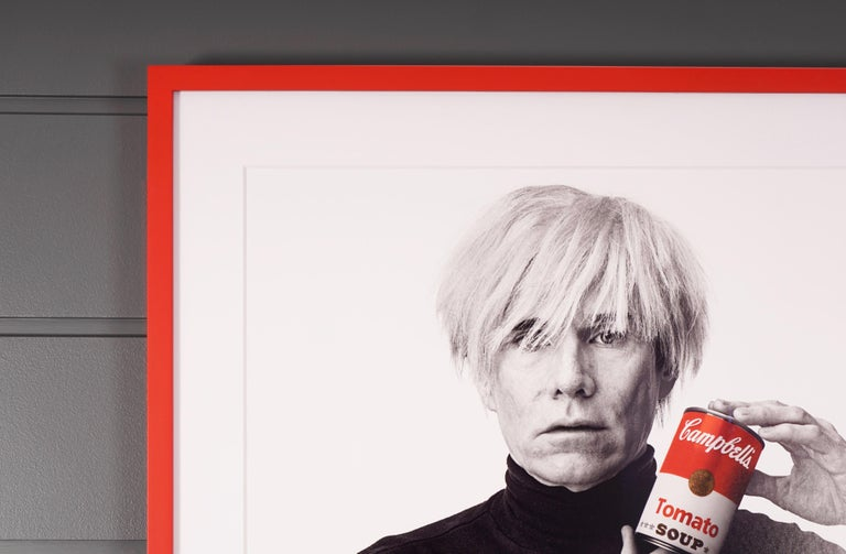 Artwork Details:  Andy Warhol with Red Campbell's Soup Can (1985/2017), photograph on archival paper, taken in 1985 by photographer Andrew Unangst. Custom framed in a bright poppy red, the dimensions measure: 35 x 37.5 x 2.25 in. / 88.9 x 95.25 x