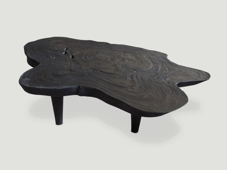 Reclaimed single slab suar wood coffee table. Charred and set on mid century style legs. A perfect combination of modern and organic.  The Triple Burnt Collection represents a unique line of modern furniture made from solid organic wood. Burnt
