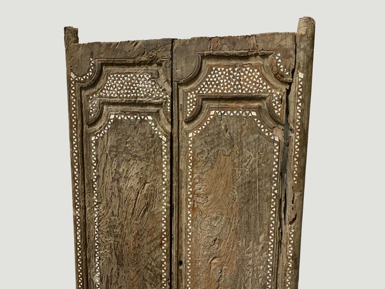 Ancient temple door that celebrates cracks and crevices found in aged teak wood. We added the shell inlay by hand. Great as a headboard, coffee table or simply as a piece of art. We currently have a large collection of temple doors available. All