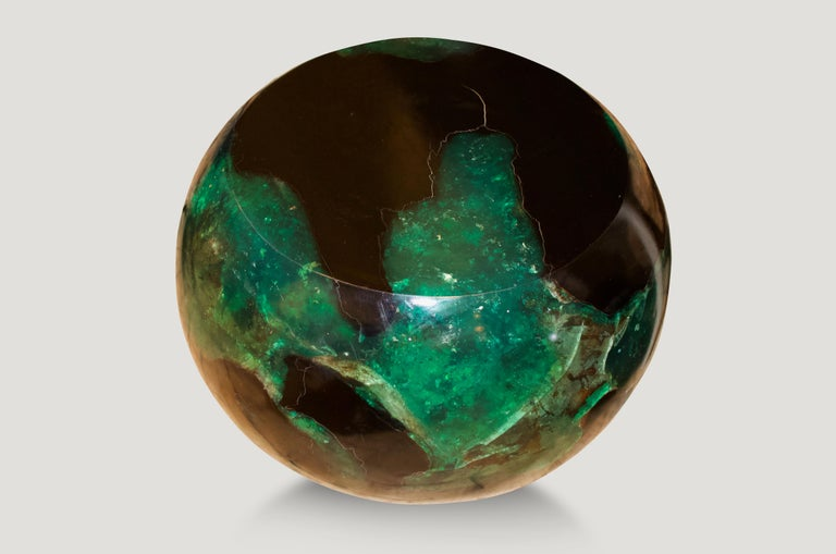 The cracked resin drum side table or stool is made from teak infused with emerald resin.  The Cracked Resin collection is a revolutionary line of modern coffee tables, side tables and dining tables made from organic teak and resin. The natural