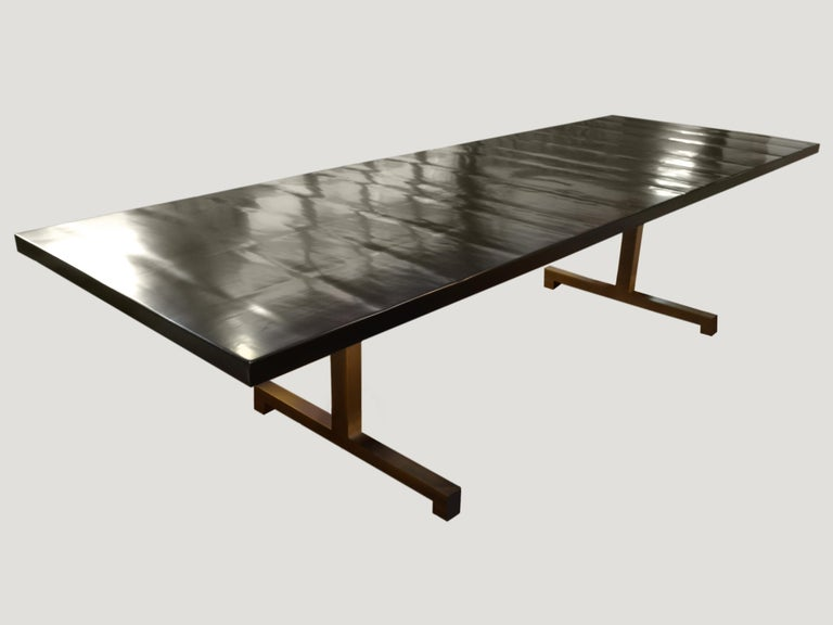 Impressive handmade dining table shown with our Minimalist cube base in a bronze-plated steel. The cherrywood top has been hand finished with a French polish rather than left completely flat and stained espresso. Also available with a live edge and