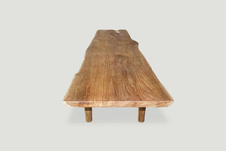 Impressive live edge reclaimed teak coffee table or bench. Stunning grain in this single two inch thick slab with a natural oil finish. We added the minimalist cylinder legs and can also increase the height for a console or dining table. Measures: