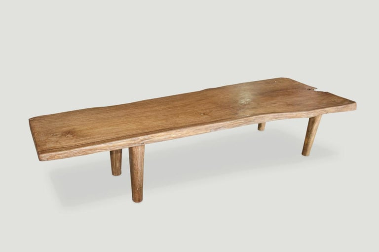 Impressive live edge reclaimed teak wood coffee table or bench. Stunning grain in this single two and a half inch thick slab with a natural oil finish. We added the midcentury style legs and can also increase the height for a console or dining