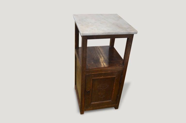 Teak wood side table with a hand carving on the small door section. The top is Italian marble. Original hardware and nice patina.