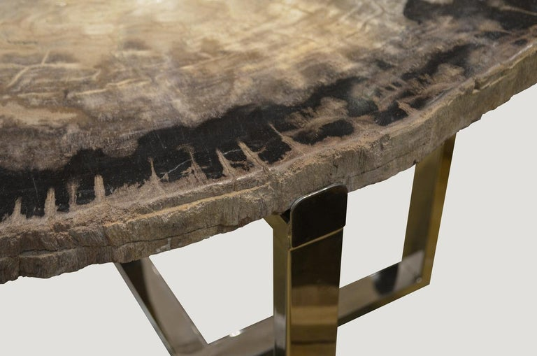 High quality petrified wood slab top side table. Stunning grey black and white tones. Set on a modern stainless steel base.  We source the highest quality petrified wood available. Each piece is hand selected and highly polished with minimal cracks.