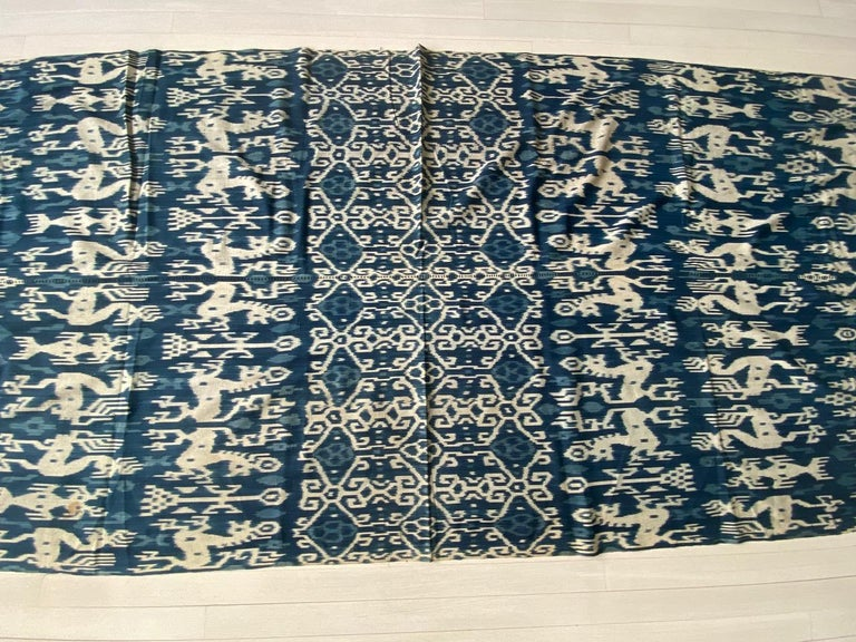 Beautiful soft indigo Ikat, with stunning long tassels, from Sumba. Fabulous on a sofa, bed or even to wear as a shawl. Mythical characters, lizards, horses and birds intermingle in this graphic cloth from Sumba. Ikat is an ancient technique which