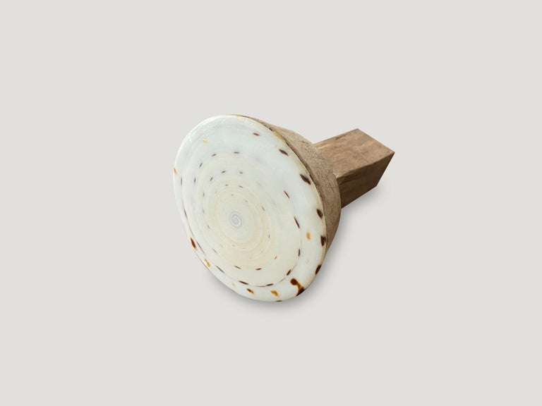We have taken the flat bottom section of a cone shaped shell and added teak wood for beautiful one of a kind door knobs. We have a collection. Great installed in bathrooms, kitchens or on cabinets as shown in the last image. The price reflects
