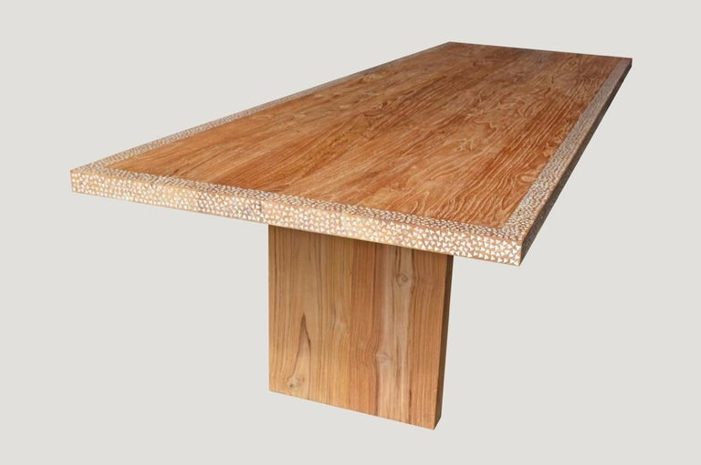 Reclaimed teak wood with added shell inlay on the top and edge, floating on modern L style base. Perfect for inside or outside dining. Hand cut shell is inlaid into the teak wood on this minimalist table. Custom sizes available.  Andrianna Shamaris.