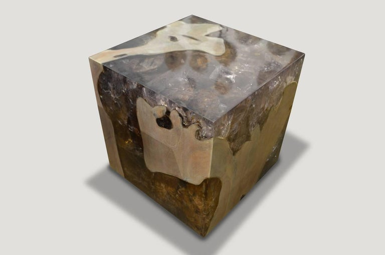 The St. Barts side table is a unique variation of the teak and cracked resin cube. Ice blue or aqua resin is first cracked and added into the natural grooves of the bleached teak wood, sanded and finished with a high polish. Handmade from reclaimed