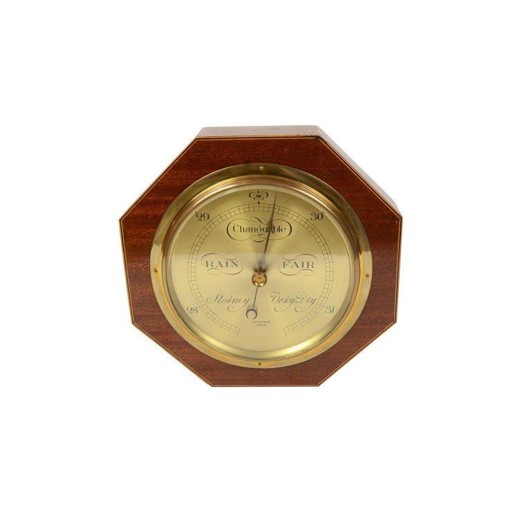Aneroid barometer, wooden octagonal shaped, brass and glass, signed Aitchison, London, 1920s. In order. Measures cm: 23 x 23 inches 9 x 9.  It's an antique measuring instrument having an element sensitive to pressure, a metal box, named barometric
