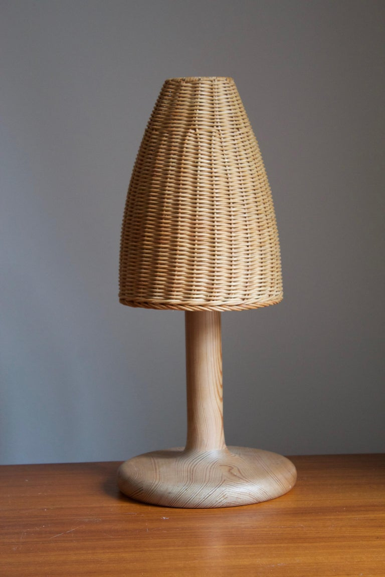A table lamp designed and produced by Aneta. In solid pine. Assorted vintage rattan lampshade. With makers label.