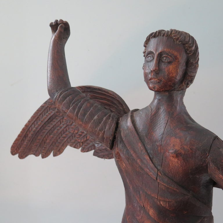 An animated striding angel of carved and pieced wood. One arm is lifted as if holding a sword as seen in paintings. The previous owner had a wooden sword made as a replacement (pictured). The head was carved separate to the body as well the arms and