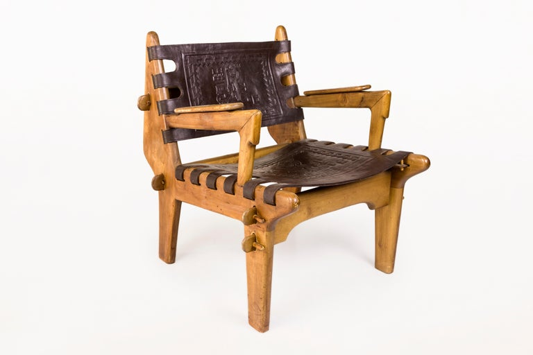 Angel Pazmino, pair of armchairs with side table, wood and leather, circa 1970, Brazil. Armchair: Height 70 cm, seat height 35 cm, width 63 cm, depth 70 cm. Table: height 44 cm, width 41 cm, depth 41 cm.