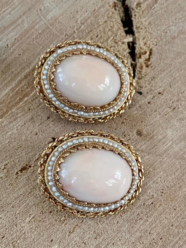 Fabulous vintage Angel Skin coral clip-on earrings are set in 14k gold with a seed pearl halo. They are stamped 14k. The oval Angel Skin Coral Cabochon stone size is 18 x 14 mm. The earrings measure 1 1/8