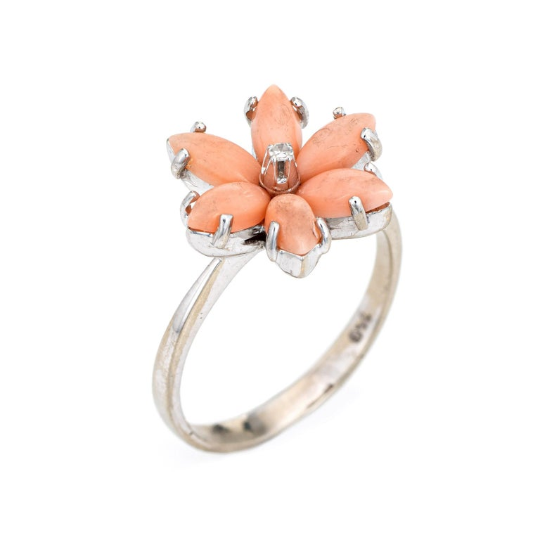 Stylish angel skin coral flower cocktail ring crafted in 18 karat white gold.   Cabochon cut coral measures 6mm x 3mm (estimated at 0.25 carats each - 1.50 carats total estimated weight). One estimated 0.01 carat (estimated at H-I color and SI1