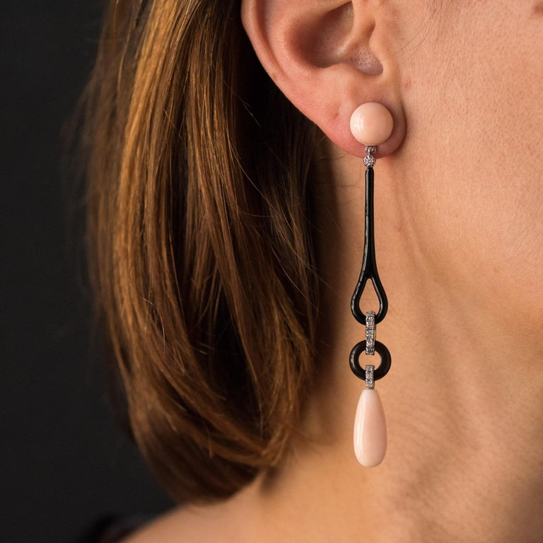 For pierced ears. Earrings in 18 karats white gold. Long dangle earrings, they consist of a pink angel skin coral cabochon that retains a long pattern of black enamel, topped with a diamond. At its base, a knot set with diamonds retains a disc of