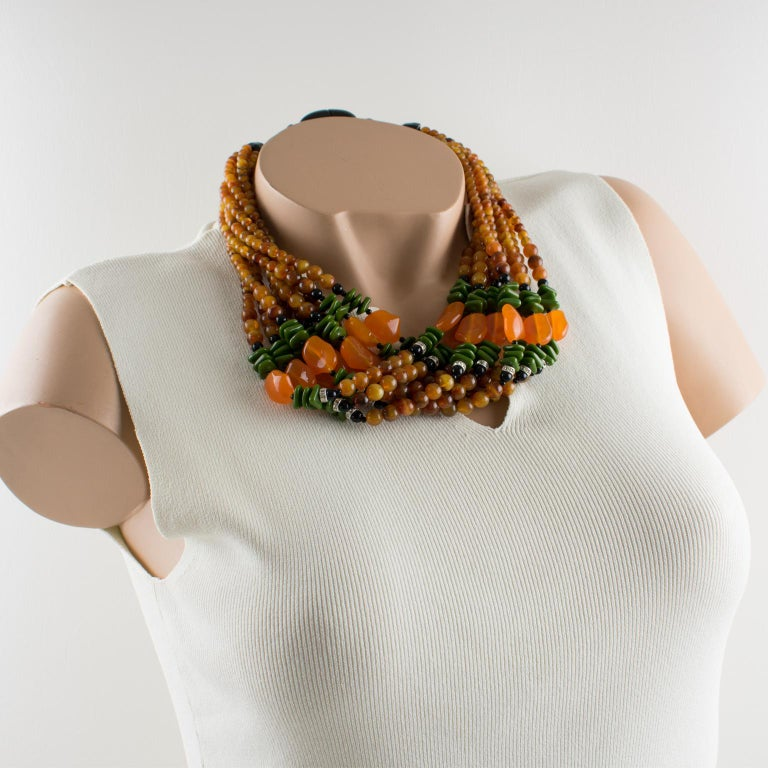 Striking Angela Caputi, made in Italy multiple strands beaded necklace. Three colors resin beads with nine strands. Assorted color range with yellow saffron marble, olive green, translucent orange and black and compliment with clear rhinestones ring