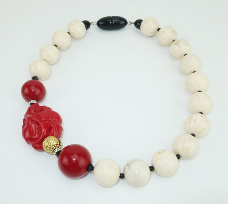 A beautiful statement making necklace from Italian designer, Angela Caputi.  The Asian inspired design is reminiscent of Art Deco creations with a combination of resin beads in shades of ivory, onyx and coral or cinnabar.  A subtle touch of crystal