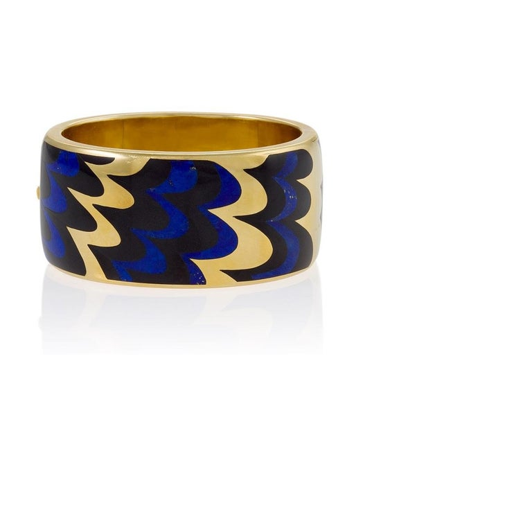 An American Late-20th Century 18 karat gold hinged bangle by Angela Cummings. The gold bangle is specially inlaid with hard stones - a great technical innovation of the time, and achievable only by the most skilled of jewelers - of lapis lazuli and