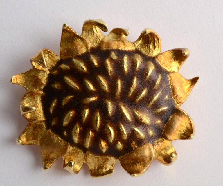 This 18 karat gold and enamel Sunflower brooch by Angela Cummings is wonderfully textured and dimensional. The height of the enamel floral center is intentionally irregular as are the triangular shaped petals. The brooch measures 1 5/8 inches in