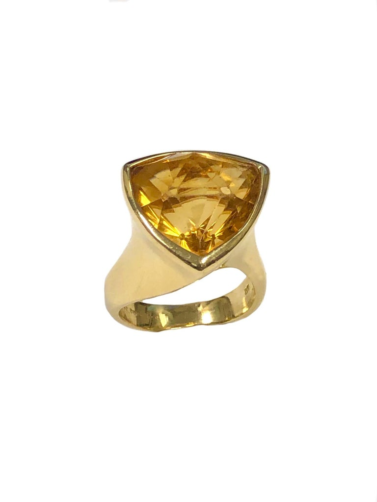 Circa 1980 Angela Cummings 18K Yellow Gold Ring, set with a very unusual shape, faceted Golden Yellow Orange Citrine of approximately 10 Carats, the top of the ring measures 3/4 X 3/4 Inch. Finger size 7 3/4. This Ring is most likely a one off, non