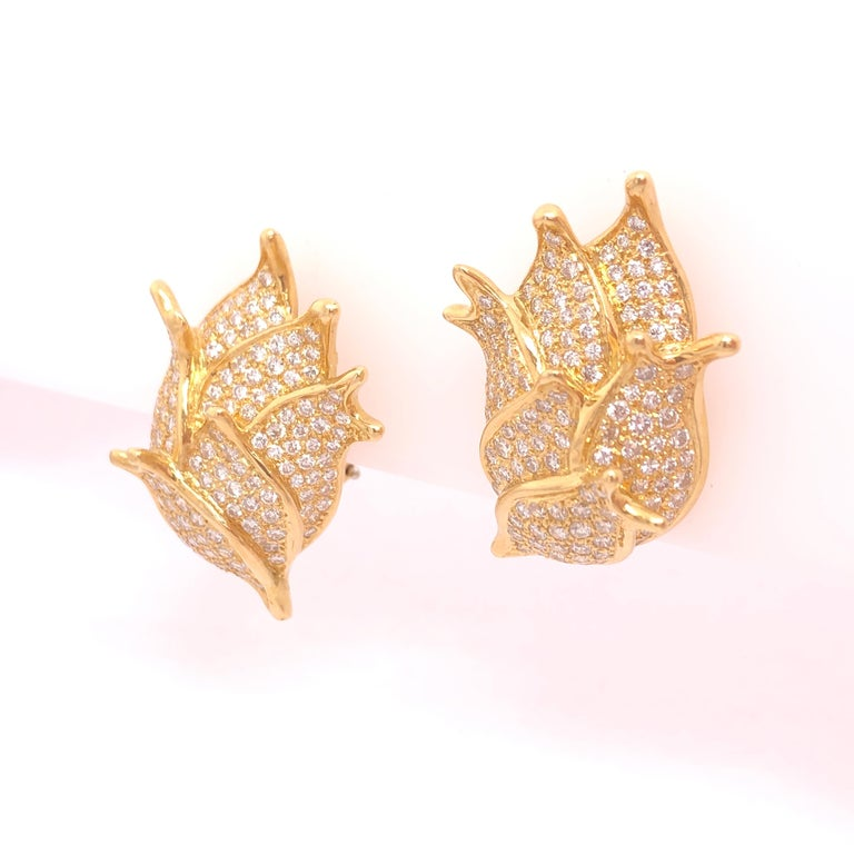 At first glance this beautiful pair of earrings resemble a flower bud or sea shell. Upon closer inspection you start to realize the earrings are composed a cluster of diamond encrusted fish. The total diamond carat weight is approximately 3.50 CT.