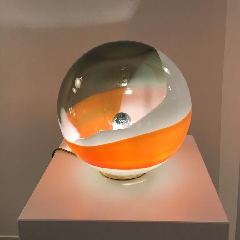 """This eye-catching table lamp, model Bolla"""", is an original vintage piece by Angelo Brotto, manufactured by Esperia in Italy around 1980.  Made of high quality glass in orange, white and clear, molded into a beautiful circle emiting a warm light"""