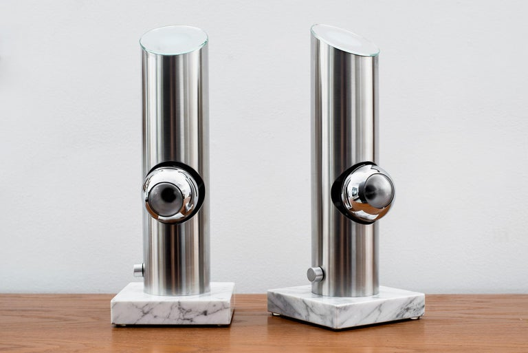 Two table lamps attributed to Angelo Lelii with marble base and brushed stainless steel structure, magnetized luminous globes in chromed steel and upper diffuser in mirrored glass. Manufactured by Arredoluce, Italy, 1969 Newly restored and