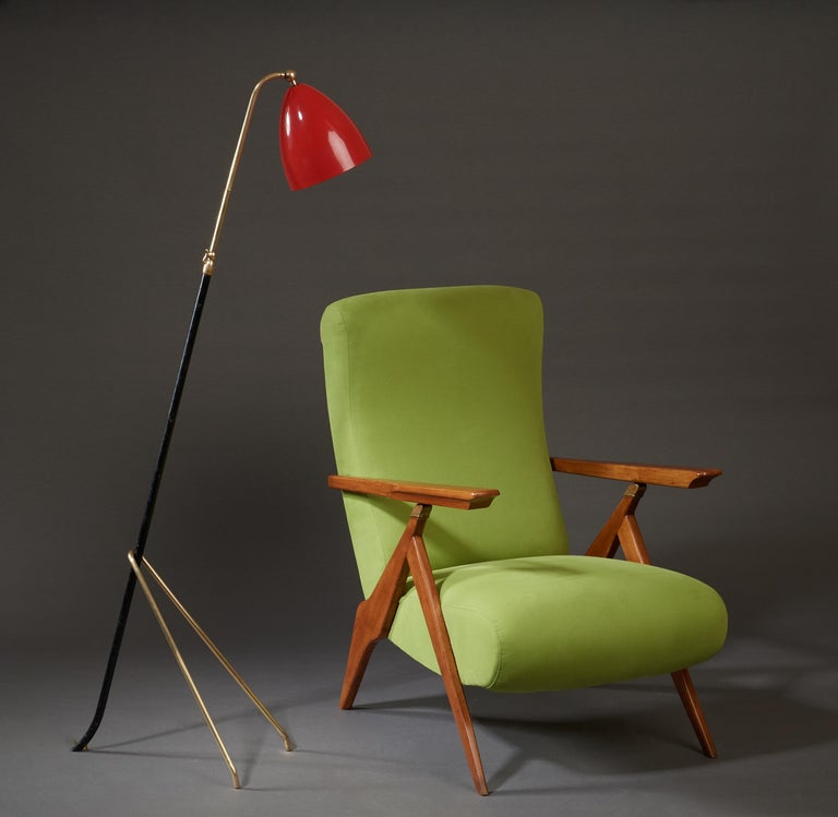 Angelo Lelii (1911-1979)  An elegant, adjustable floor lamp by Angelo Lelii (sometimes spelled Angelo Lelli), for his pioneering lighting firm Arredoluce. A graceful tripartite base curves two polished brass forelegs around a black-lacquered iron