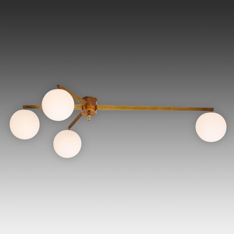 Angelo Lelli for Arredoluce original striking Stella flush mount ceiling light or chandelier with four opaline glass globe shades suspended from rich patinated brass structure and mount. Truly a design icon with clean architectural lines. Fully