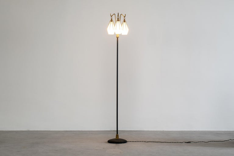 Beautiful floor lamp with three glass lampshades, designed by Angelo Lelii for Arredoluce, 1950s. This lamp presents a painted metal structure with three lampshades in satin glass and brass details.  Manufacturer's brand stamped under the base of