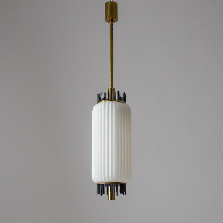 Very rare Angelo Lelii pendant for Arredoluce, circa 1959. Composed of a large ribbed satin glass diffuser and brass hardware with graphical black lacquered brass finials on both ends of the glass. Very fine original condition with some patina on