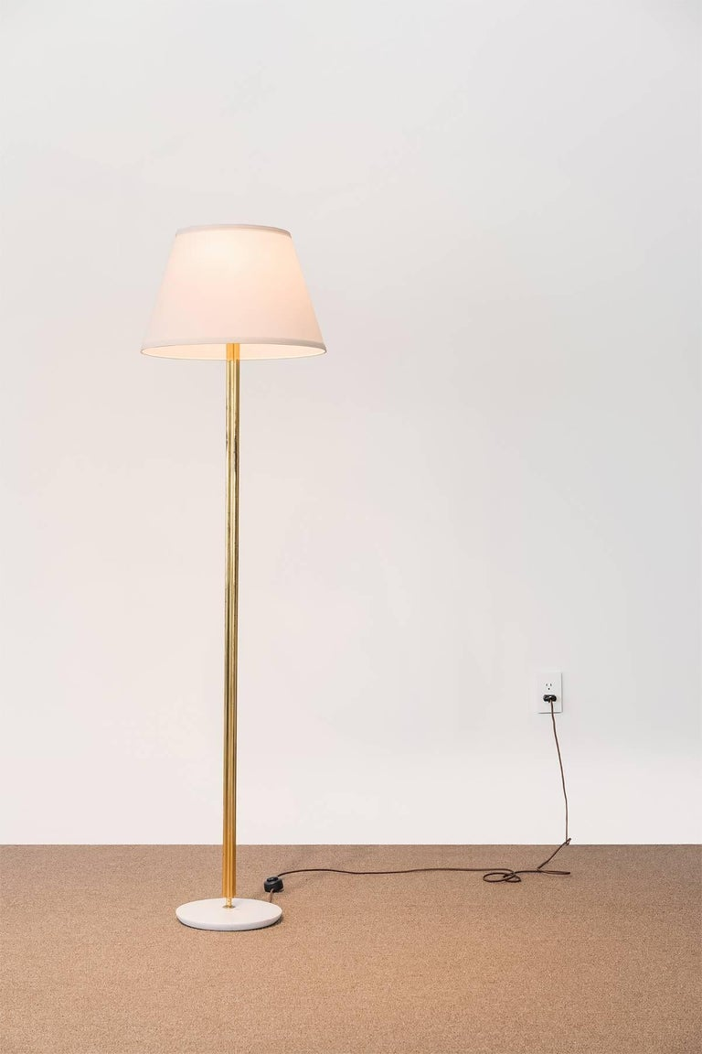 A floor lamp attributed to Italian designer Angelo Lelii for Arredoluce, Italy. Brass rod, marble base.   Fontana Arte was co-founded by Gio Ponti and is also known for producing works by creators such as Angelo Leeli and Max Ingrand.   In the past,