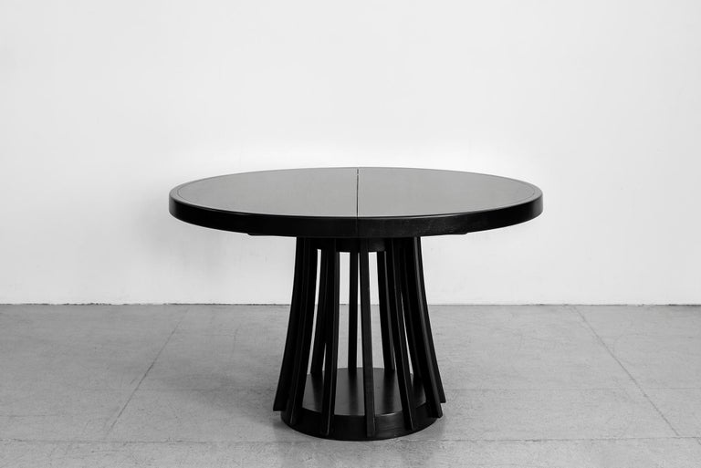 An extendable dining table by Angelo Mangiarotti manufactured by La Sorgente Dei Mobili, 1972. Rosewood, extendable tabletop, professionally refinished in ebony.  Extension mechanism folds the leaf out from underneath center of table.