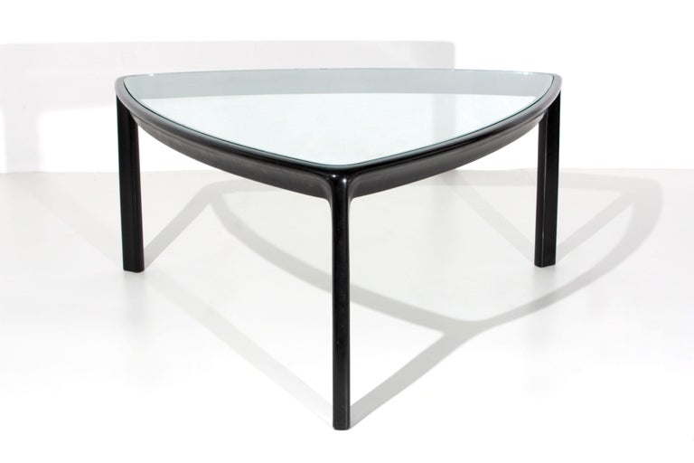 Large table designed by Angelo Mangiarotti for the Skipper production. The table has a slightly rounded triangular shape. Its structure is in wood with three pedestals. As a support base we find a glass top. The table is ideal to define living room