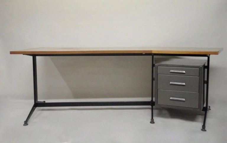 Executive desk manufactured by Tecno comprises a squared boomerang shaped wood top, a black enameled base with brass feet and three grey enameled metal pull-out drawers.