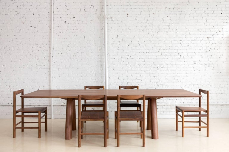 This contemporary, minimal walnut dining table produced in 2017 features large diameter legs and a bold trestle to give rise to an elegant hardwood top. Top includes rounded corners with an optional underside bevel to compliment details found on the