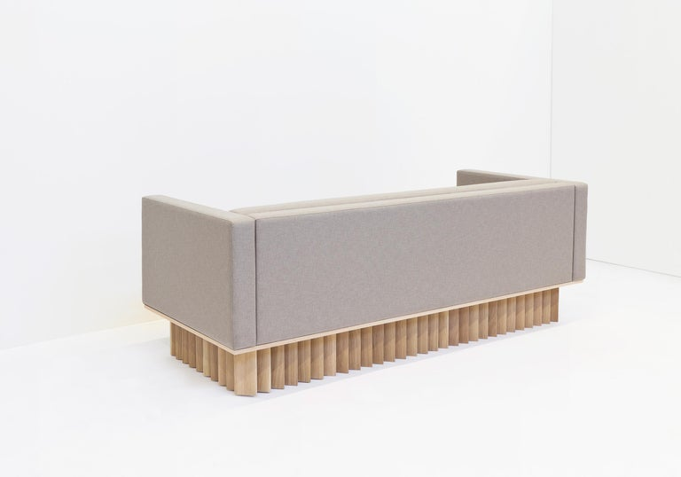Through carefully considered angled cuts, rotation and spacing, solid blocks of wood are transformed into a sofa platform that creates a playful, gradual shift in color and form from various vantage points. Pictured in solid white oak with a hand
