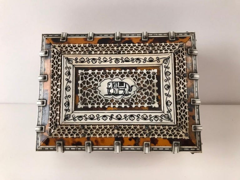 19th century Anglo-Indian desk-top box made of sandalwood veneered with tortoiseshell overlaid with intricate pierced bone panels and banding on four lion's paw feet. The central panel on top decorated with a incised drawing of an elephant in black