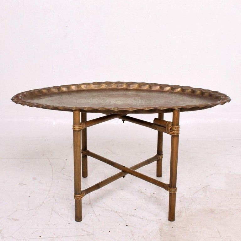 For your consideration a vintage coffee table made of bamboo base and scalloped brass tabletop in oval shape.   Original vintage patina. Great character.  19 1/4