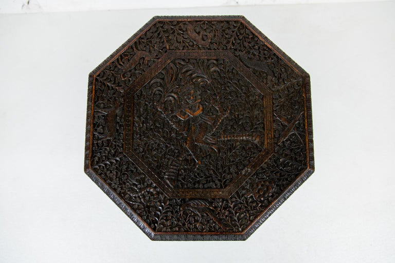 Anglo-Indian carved octagonal teak wood table, top is carved with a flute player in the central cartouche. It is bordered with stylized deer, dogs, birds, pine cones, and salamanders.