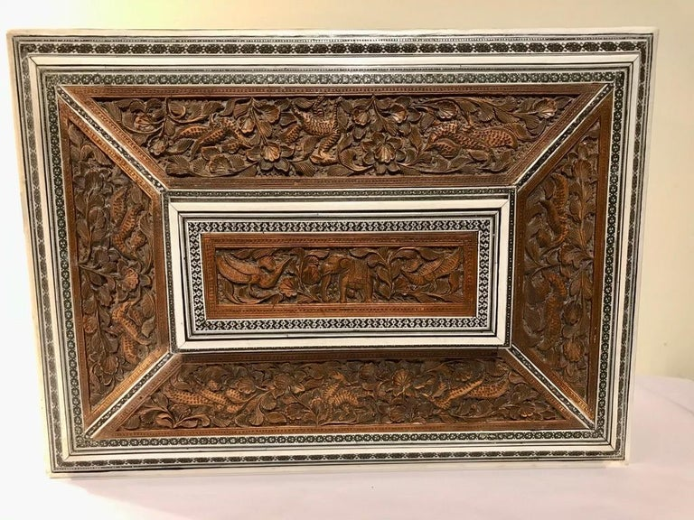 The lid with a centrally carved elephant surrounded by birds and foliage, framed by inlaid bone, ebony and mother of pearl. The other panels of the top and sides with other animals and birds. The sarcophagus shape resting on four silver paw feet,