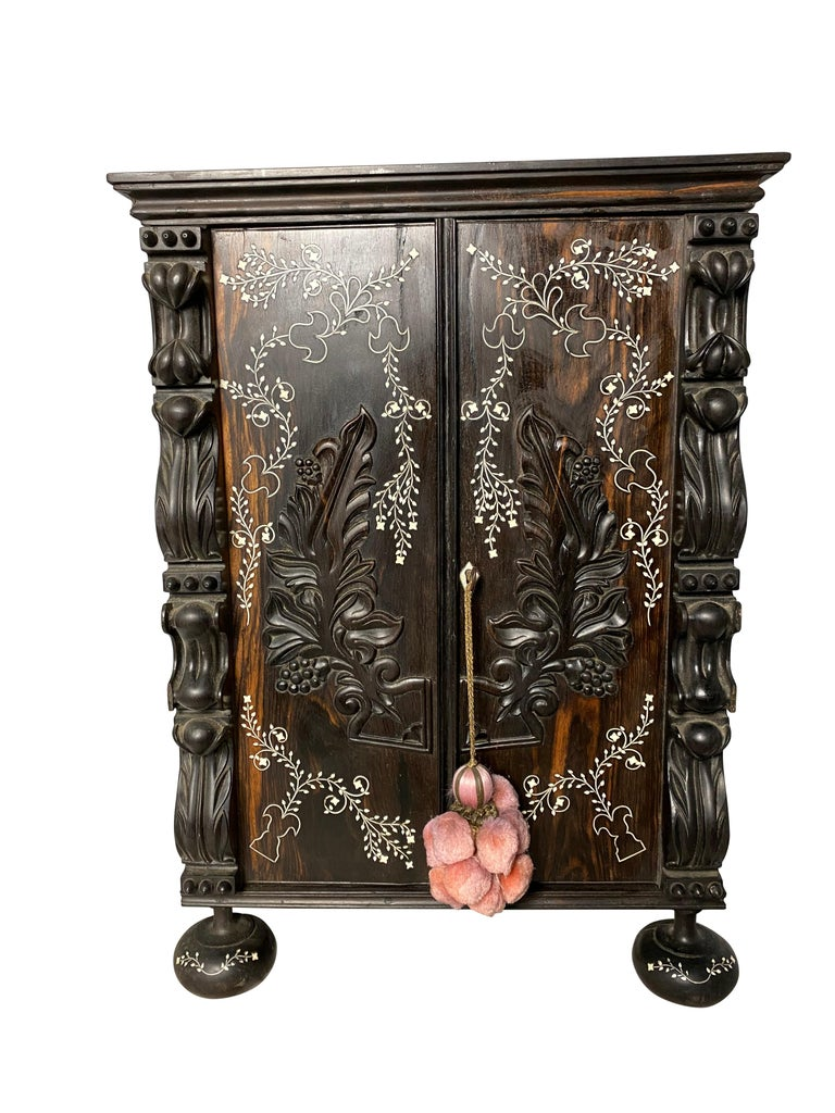 A dark Anglo-Indian ebony inlaid cabinet from the 19th century. With large spaces inside for storage and with both floral carvings and embellishments, this cabinet is suitable for both decoration and use. 