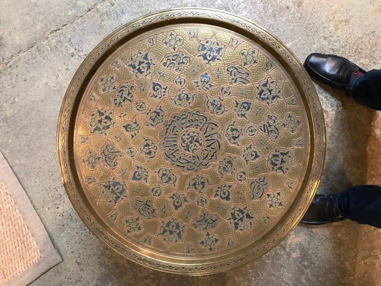 This Anglo-Indian table has a folding base that goes from 6 legs into 2. It was made in the 19th century and includes a round metal tray as the tabletop. The tray has blue patterns with red outlines.